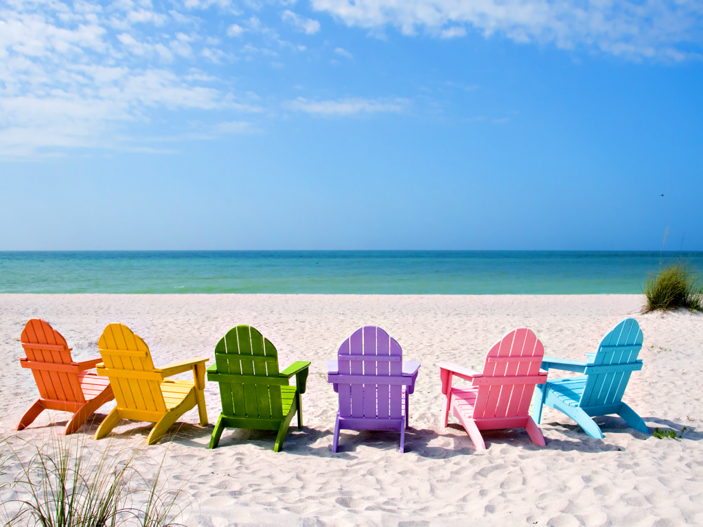 Wooden chairs of different colours in a the beach on a sunny day